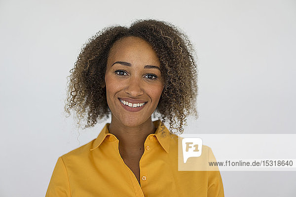 Portrait of smiling young woman wearing yellow shirt