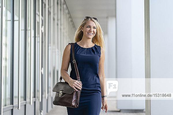Porträt einer lächelnden blonden Geschäftsfrau mit Aktentasche in blauem Sommerkleid
