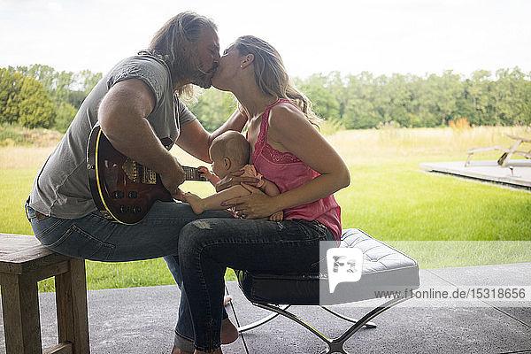 Mann mit Gitarre küsst Frau mit auf dem Schoß sitzendem Mädchen