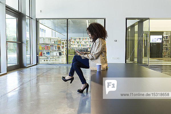 Junge Geschäftsfrau mit Kaffee zum Mitnehmen mit Tablette
