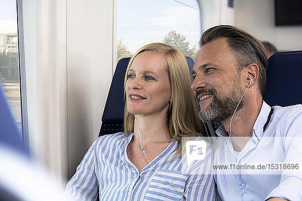 Ehepaar reist mit dem Zug und schaut aus dem Fenster