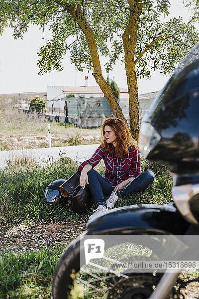 Motorcyclist having cigarette break under a tree