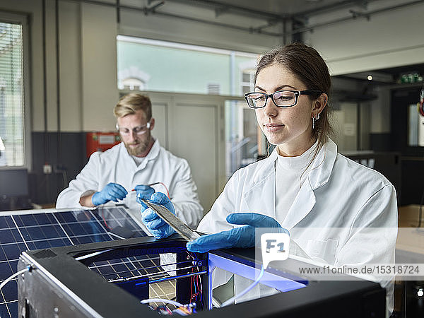 Two technicians working on solar cell in lab