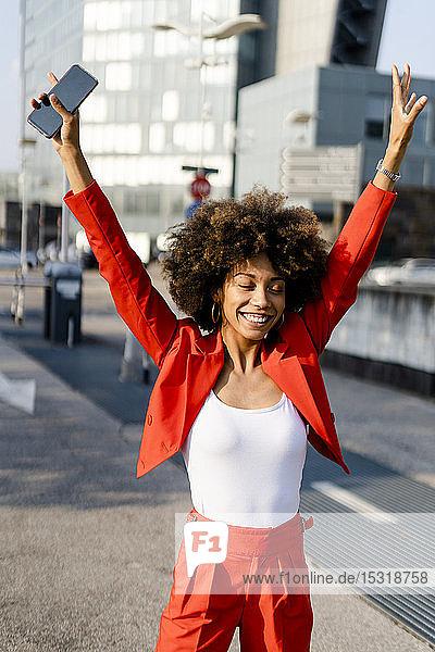 Porträt einer glücklichen jungen Frau mit Smartphone in modischem roten Hosenanzug