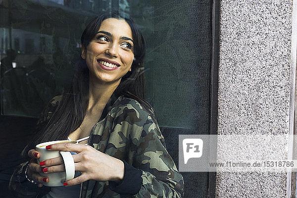 Junge Frau sitzt im Café mit einer Tasse Kaffee und schaut aus dem Fenster