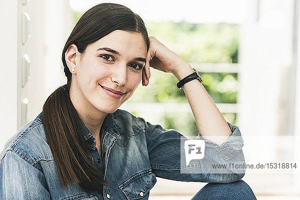 Porträt einer lächelnden jungen Frau  die zu Hause ein Jeanshemd trägt