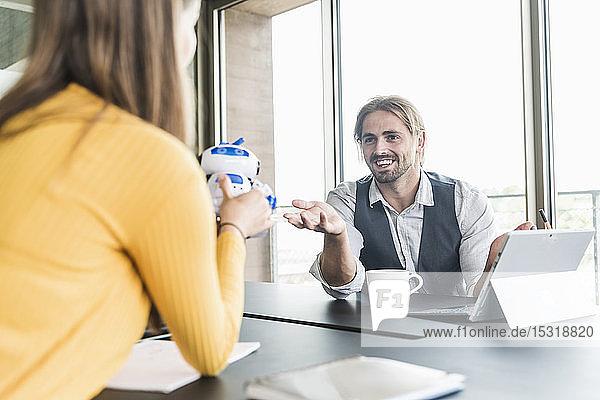 Junger Geschäftsmann und junge Geschäftsfrau mit Roboter sitzen am Schreibtisch im Büro und unterhalten sich