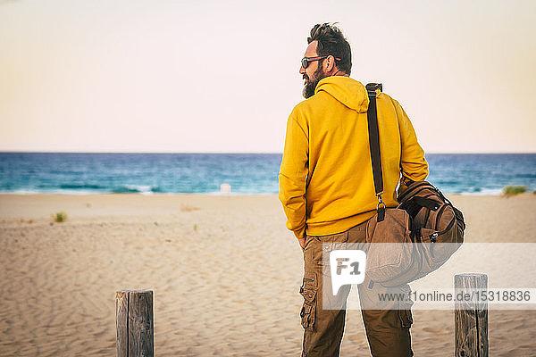 Mann mit gelbem Kapuzenpullover und braunem Korb