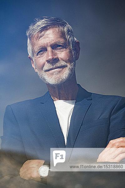 Portrait of senior businessman behind windowpane
