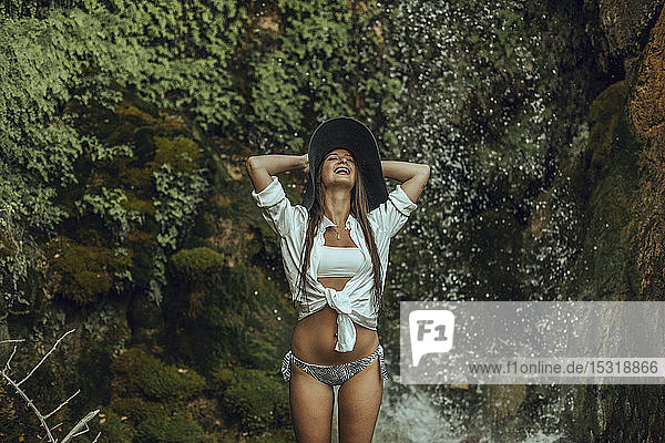 Happy young woman wearing a hat standing near a waterfall