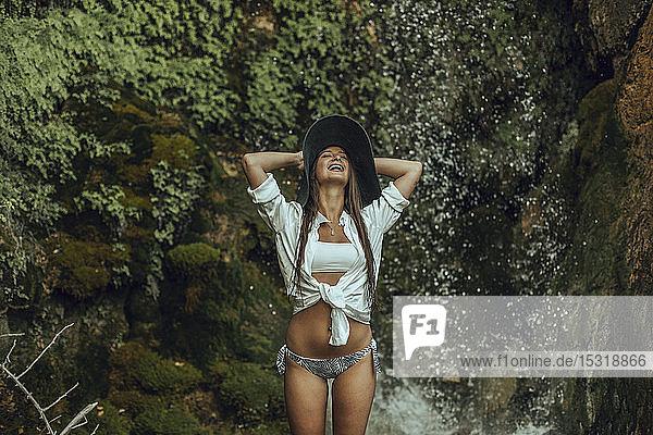 Glückliche junge Frau mit Hut  die in der Nähe eines Wasserfalls steht