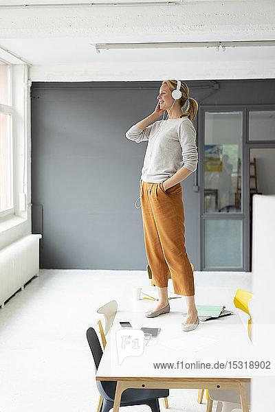 Junge Geschäftsfrau  die im Büro auf dem Schreibtisch stehend mit Kopfhörern Musik hört