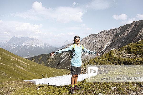 Junge wandert in den Bergen und geniesst die Natur