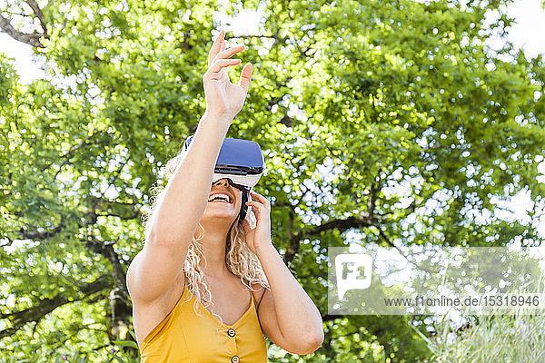 Junge blonde Frau mit Virtual-Reality-Brille im Freien