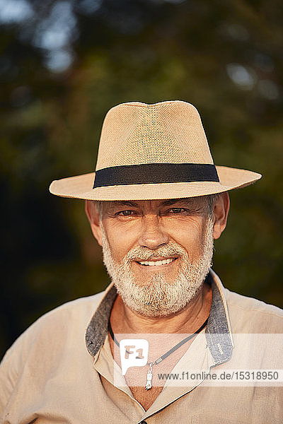 Porträt eines lächelnden älteren Mannes mit Sommerhut im Freien