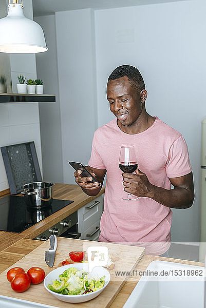 Lächelnder junger Mann mit Weinglas  der während der Salatzubereitung sein Handy benutzt