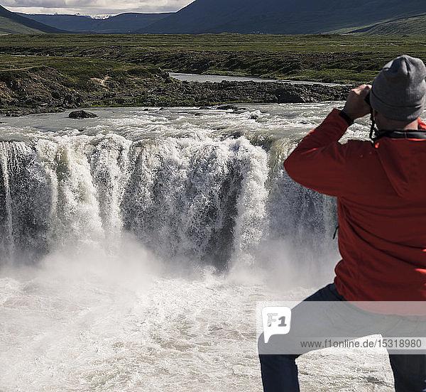 Mann betrachtet die Godafoss-Wasserfälle  Island  mit einem Fernglas
