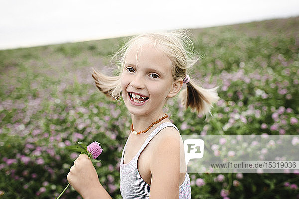 Laughing girl holding clover flowers