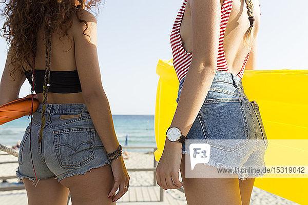 Junge Frauen mit gelbem Luftbett gehen an den Strand