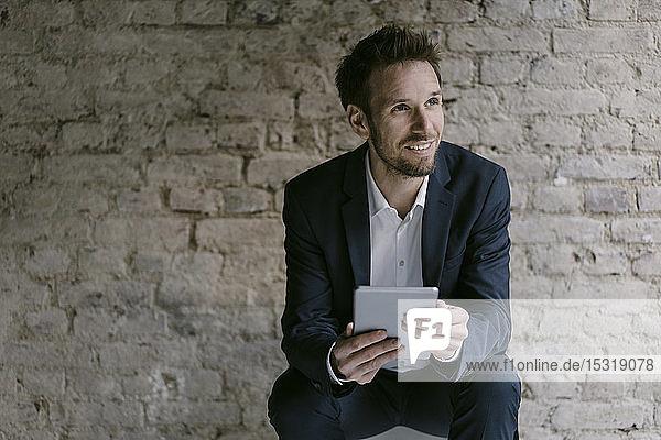 Porträt eines lächelnden Geschäftsmannes mit Tablette