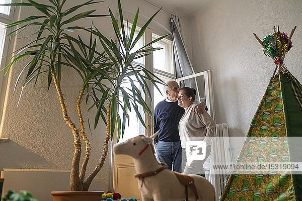 Älteres Paar küsst sich am Fenster im Kinderzimmer