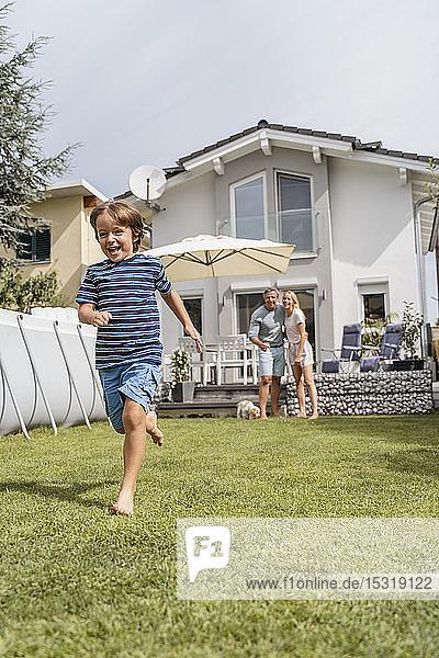 Boy running in garden with parents watching