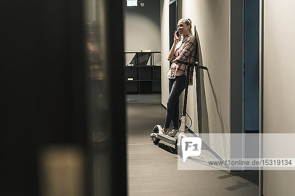 Smiling businesswoman with e-scooter talking on cell phone in office