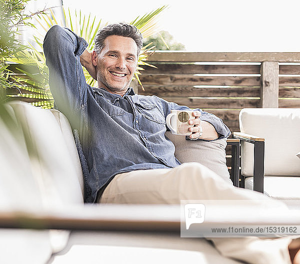 Confident man relaxing on the terrace  drinking coffee