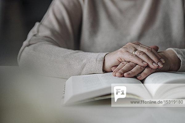 Nahaufnahme einer älteren Frau  die ein Buch auf dem Tisch liest