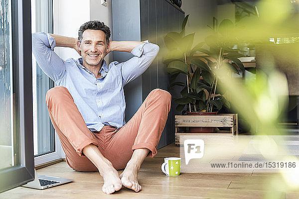 Reifer Mann entspannt sich zu Hause bei einer Tasse Kaffee  mit Laptop