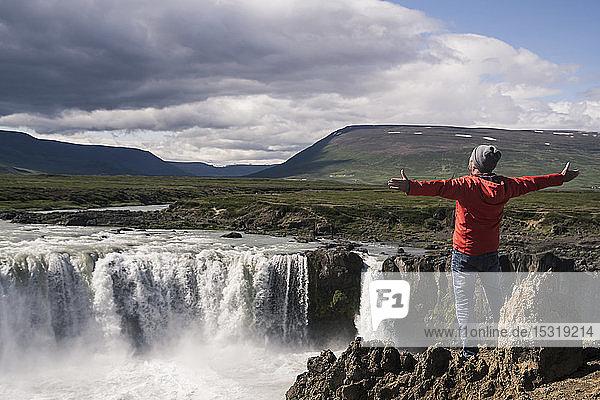 Mann betrachtet Godafoss-Wasserfälle  Island  mit ausgestreckten Armen