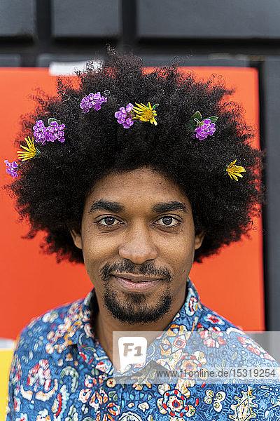 Bildnis eines Mannes mit Blüten im Haar und farbigem Hemd