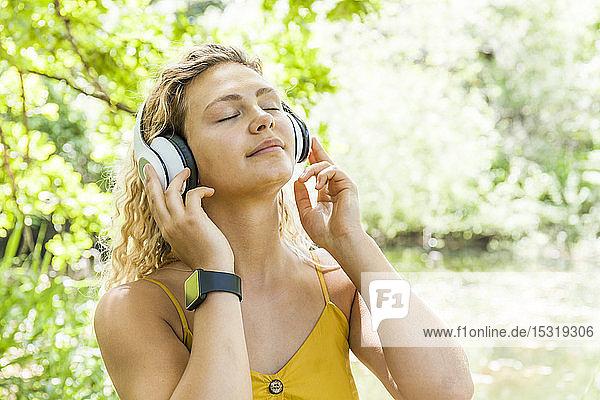 Lächelnde Frau mit geschlossenen Augen  die am Seeufer Musik hört