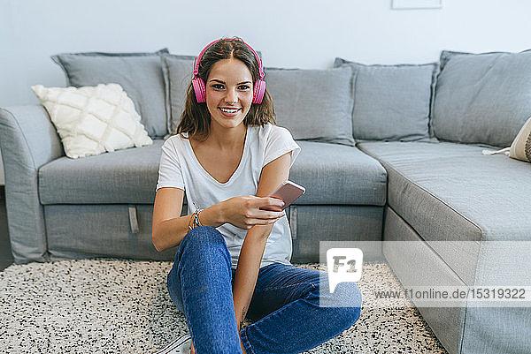 Porträt einer lächelnden jungen Frau,  die im Wohnzimmer auf dem Boden sitzt und mit ihrem Handy Musik hört