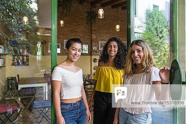 Porträt von drei lächelnden jungen Frauen in einem Cafe