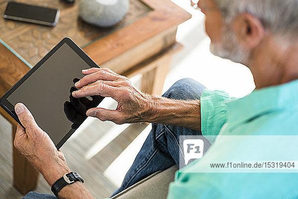 Close-up of senior man using tablet at home