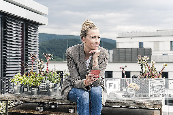 Businesswoman with cell phone sitting on roof terrace having a break
