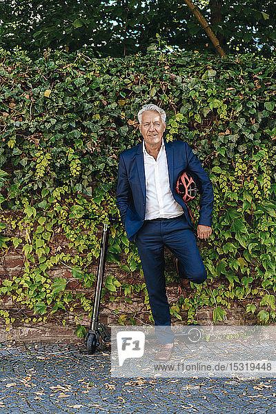 Älterer Mann mit an einer Wand lehnendem E-Scooter