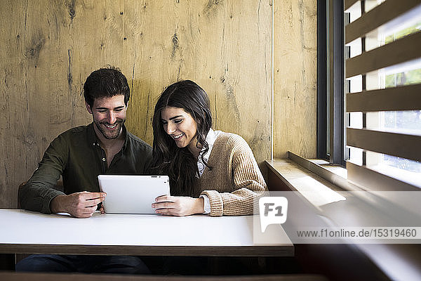 Laughing couple using digital tablet in a cafe