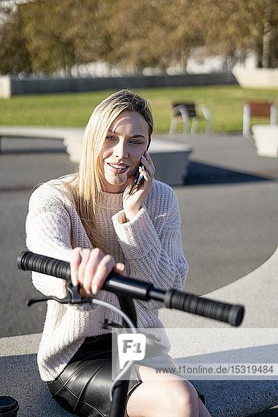 Porträt einer jungen Frau am Telefon  die auf einer Bank bei Sonnenlicht mit einem Kickroller sitzt