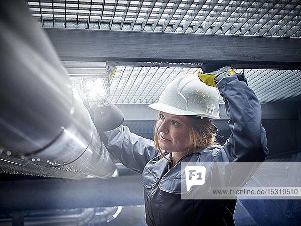 Handwerkerin mit Schutzhelm bei der Arbeit an der Pfeife