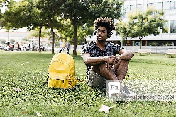 Porträt eines Mannes  der auf einer Wiese sitzt und mit schnurlosen Kopfhörern Musik hört  Barcelona  Spanien