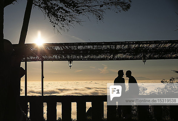 Silhouette of gay couple sitting above the clouds in backlight