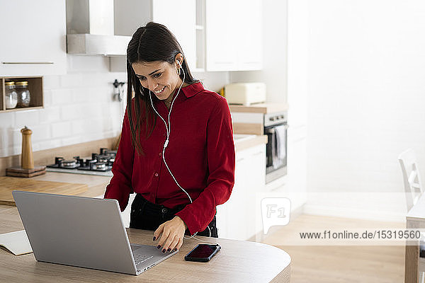 Young businesswoman with earphones using laptop at home