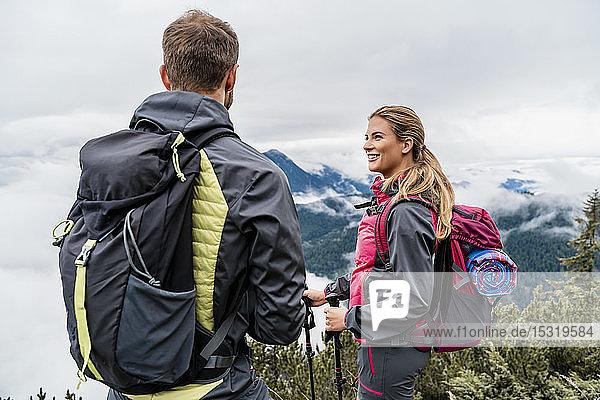 Lächelndes junges Paar auf einer Wanderung in den Bergen  Herzogstand  Bayern  Deutschland