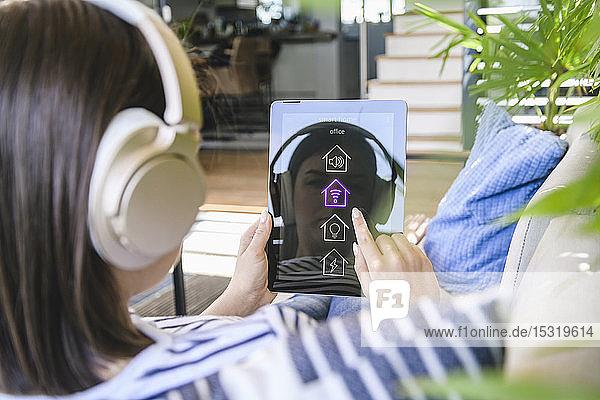 Junge Frau mit Tablett amit Smart Home Control-Funktionen und Kopfhörern
