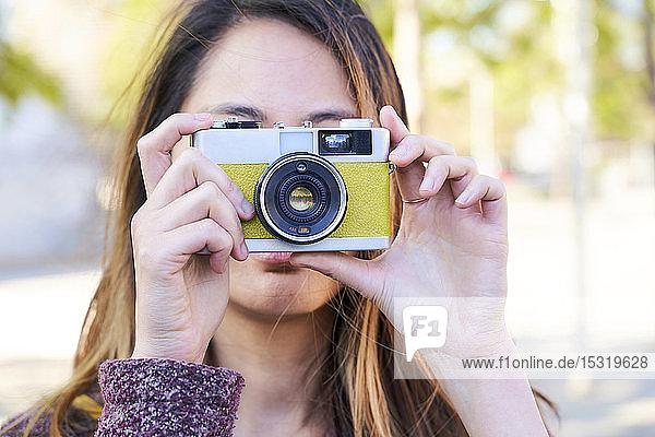 Frau  die mit einer analogen Oldtimer-Kamera fotografiert
