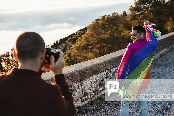 Photographer taking picture of man wrapped in a gay pride flag on a road in the mountains