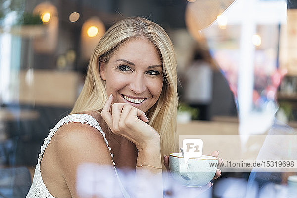 Portrait of smiling blond woman drinking coffee in a cafe