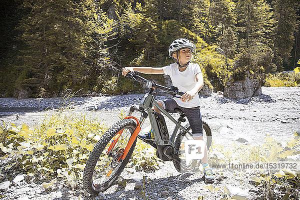 Junge in den Bergen mit seinem E-Mountainbike